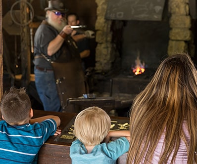 Children watching a live demonstration of the John Deere Blacksmith