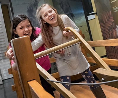 Two young girls testing their strength with the original John Deere plow interactive