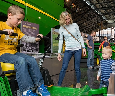Mother and father with their children looking at John Deere Lawn and Garden equipment