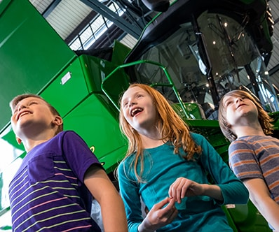 Children looking at agriculture machines at the John Deere Pavilion