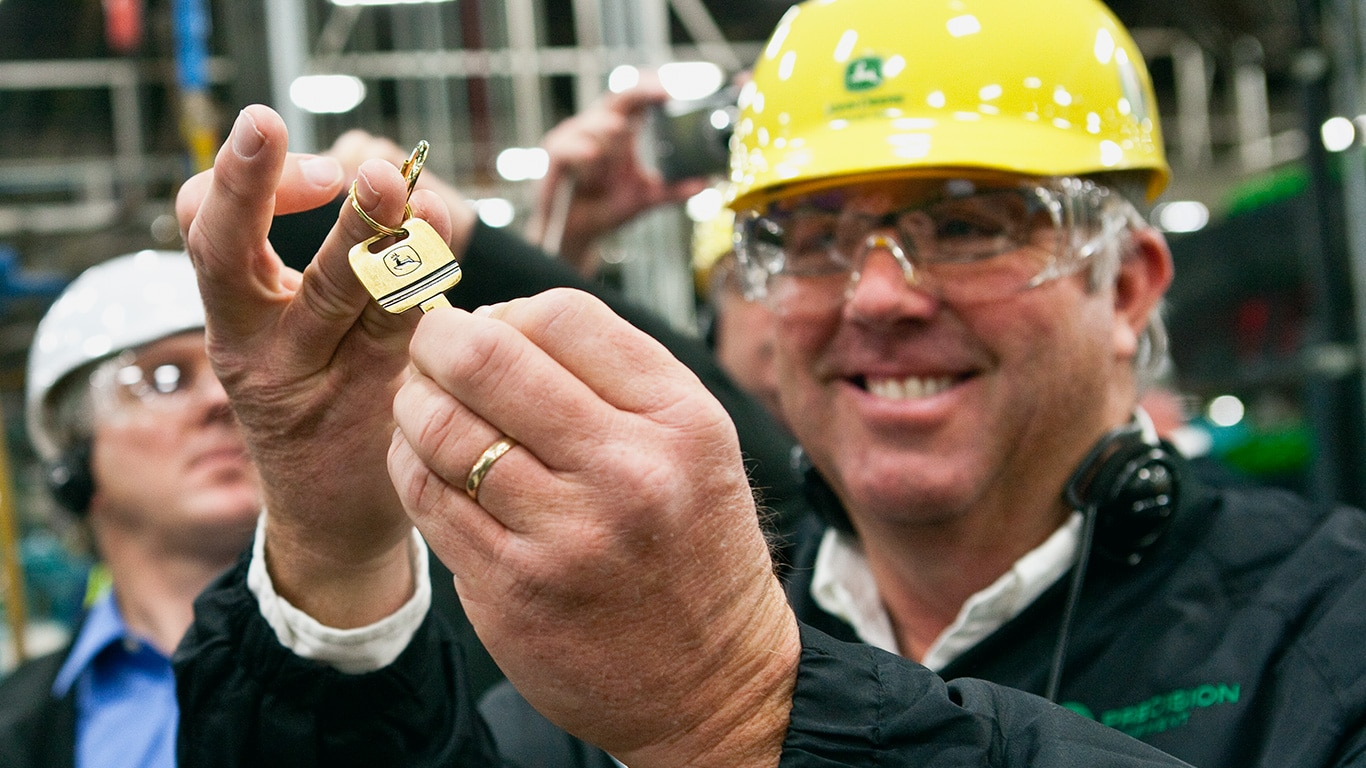 Customer holding his gold key he received at the factory