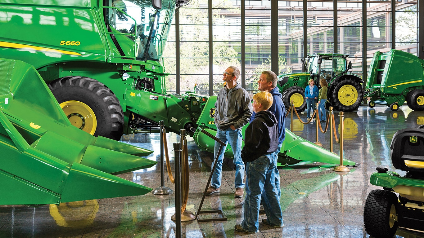 Exceptionnel ... Three People Look Up At A John Deere Combine On The Headquarters  Display Floor ...