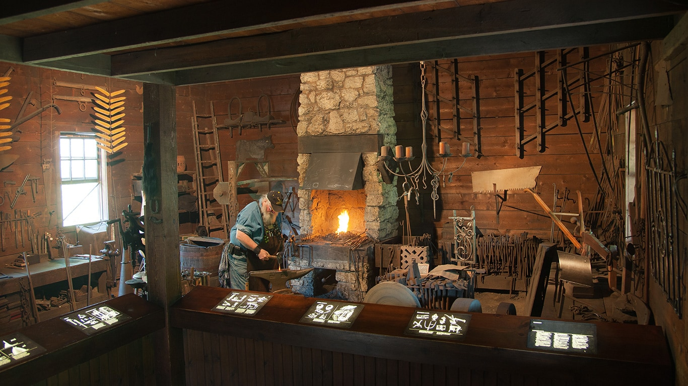 Blacksmith working inside the John Deere blacktop building