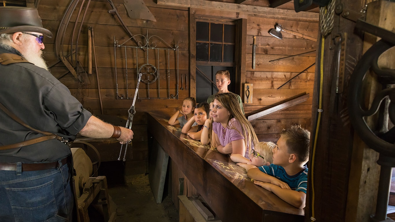 The John Deere Blacksmith is doing a live demonstration for a group of children