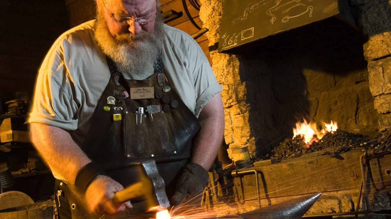 Blacksmith working inside the John Deere Blacksmith building