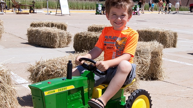 Young boy driving a John Deere pedal tractor in an obstacle course activity