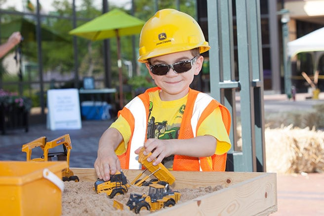 Boy playing with John Deere construction toys in sand