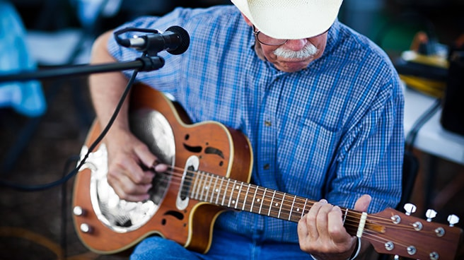 Older man with cowboy hat playing on a guitar outdoors