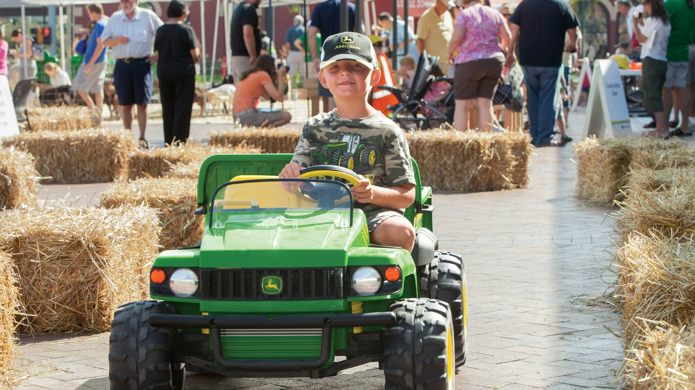 Boy driving a toy John Deere Gator at the Learn and Play Day event