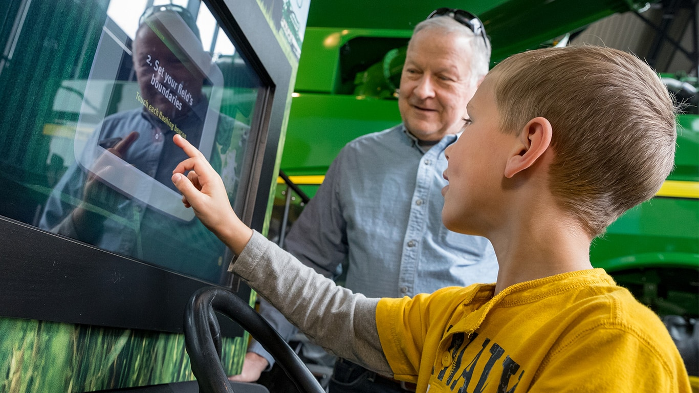 A boy touches video screen as part of an interactive agriculture exhibit