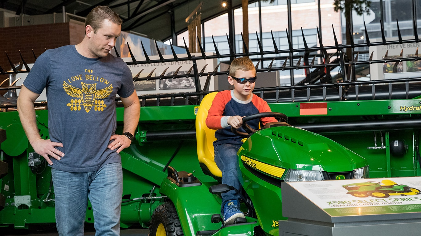 Father and son looking at a John Deere Lawn and Garden Tractor