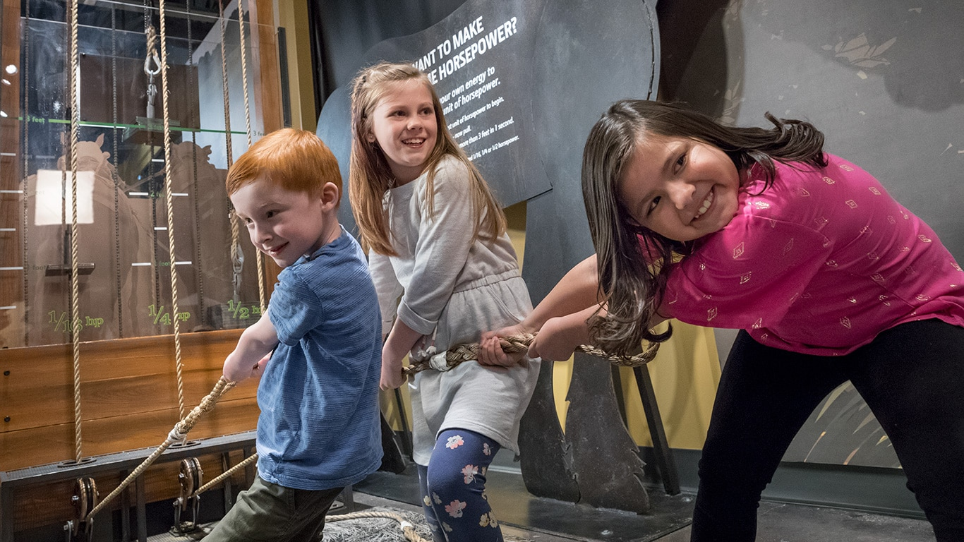 Three young children pulling ropes on an interactive display experiencing how hard it is to pull a plow