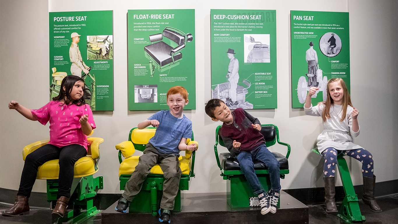 Children sitting on tractor seats from various years