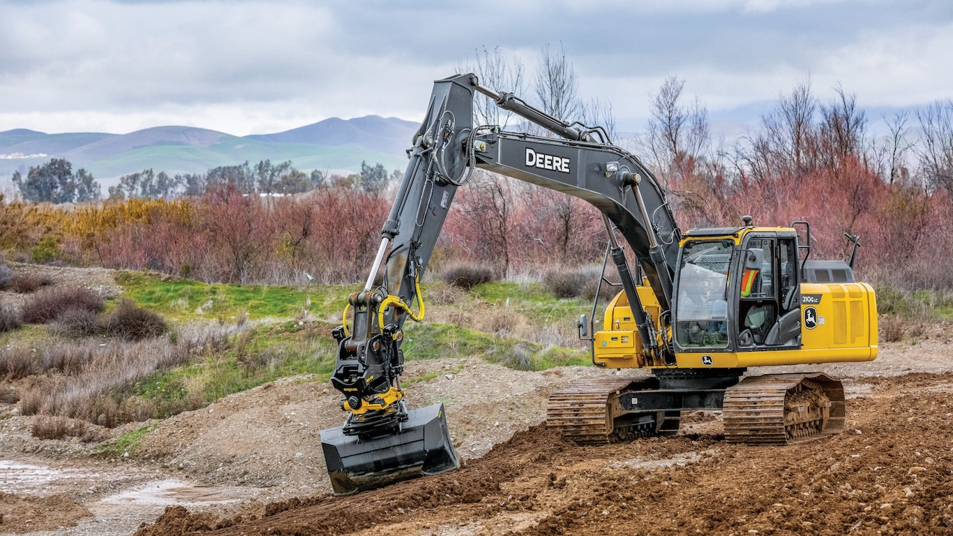John Deere Excavator equipped with an engcon tiltrotator in motion on a work site.