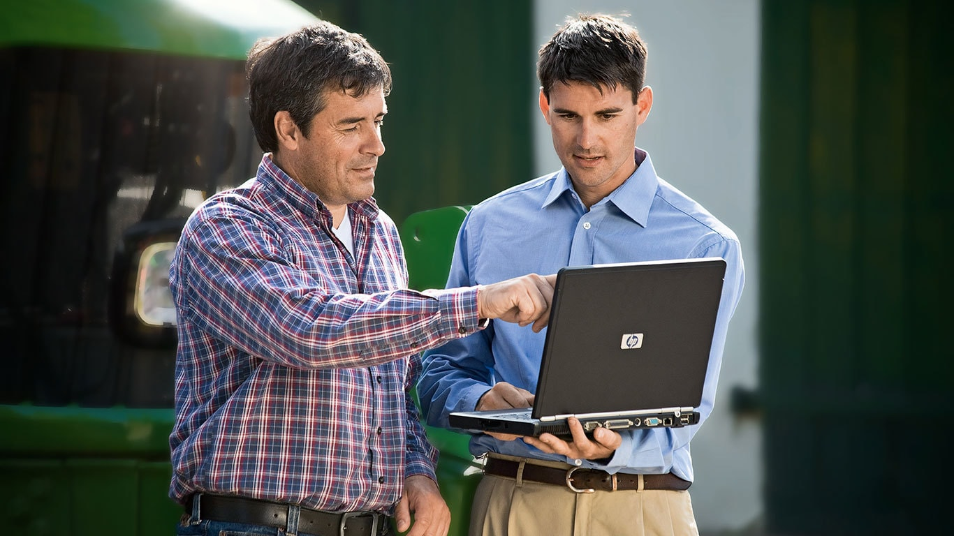 Two men talking while looking at a laptop computer