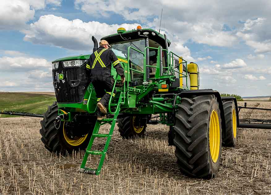 Man climbing up a John Deere tractor in a field