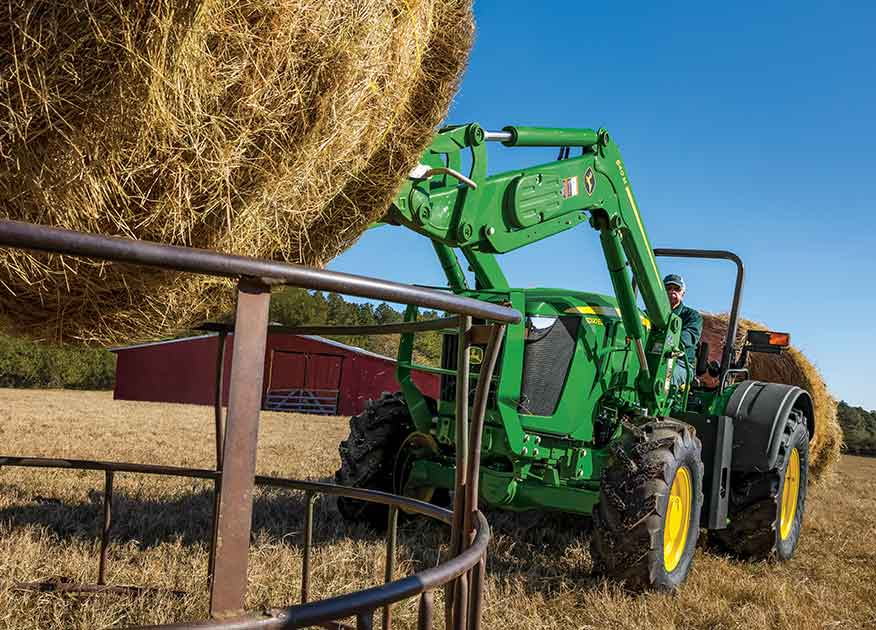 John Deere Compact Tractors licking a hay bale on a farm