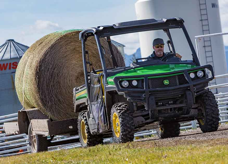 Man driving a John Deere Gator Utility Vehicle while towing a bale of hay
