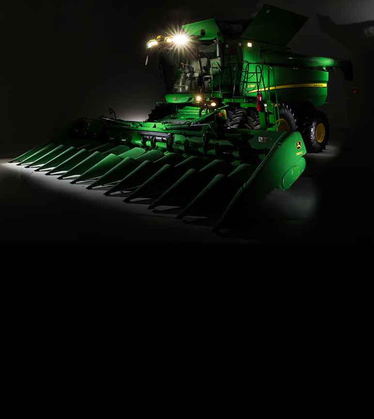 John Deere S780 Combine with lights on in a dark room