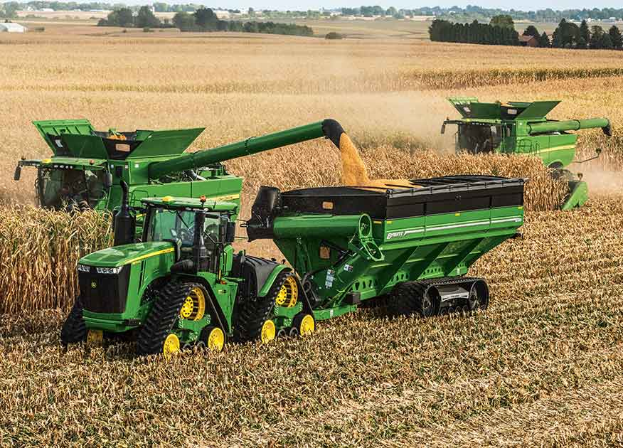 John Deere tractor and two combines working in a field