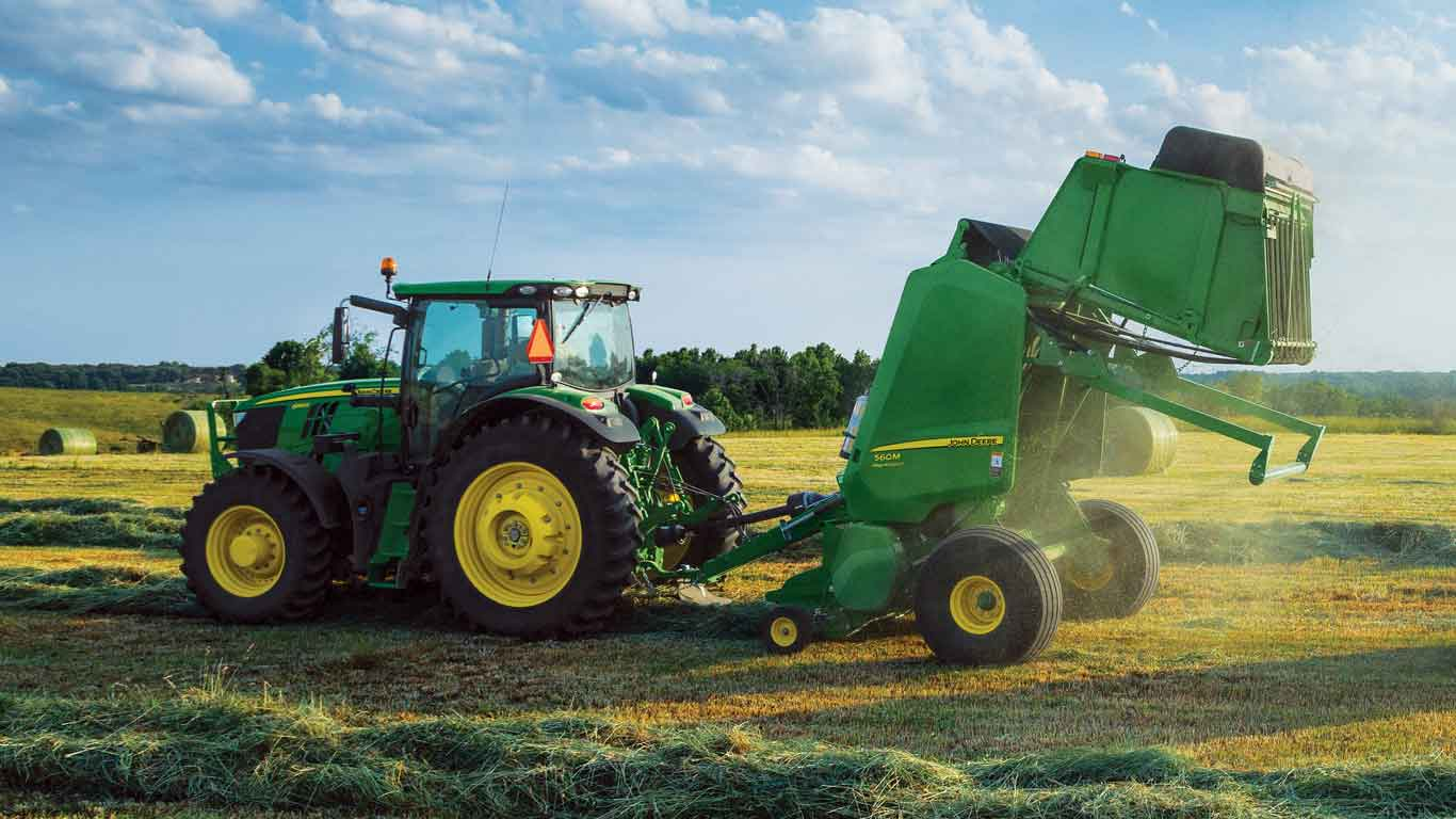 John Deere tractor with baler attachment in a field