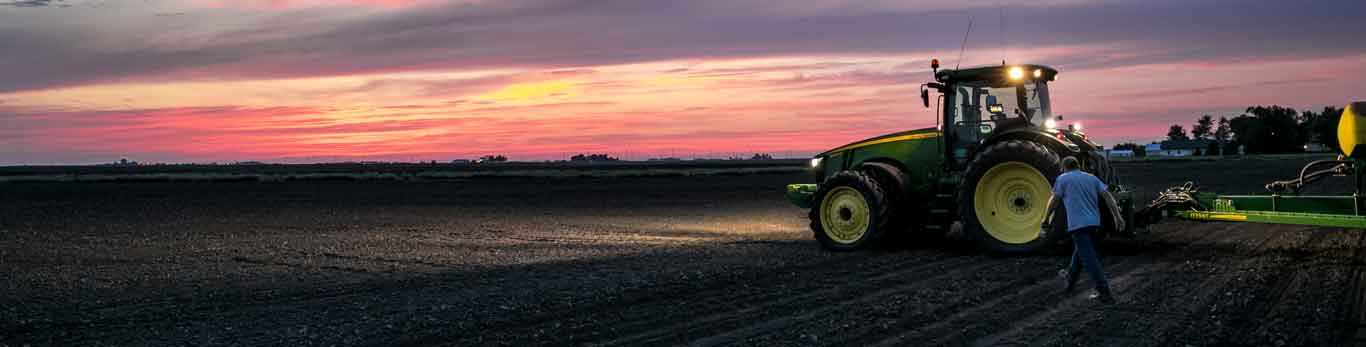 Man walking in a field next to a John Deere tractor during sunset