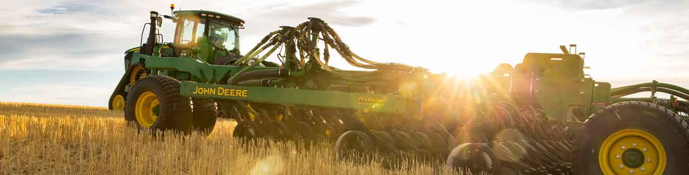 John Deere Tractor with attachment in the field during sunrise