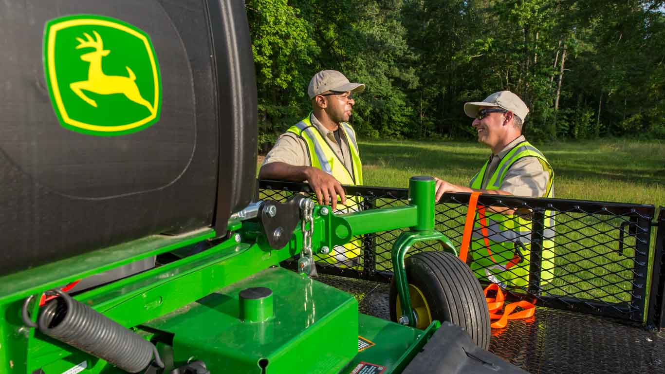 Two men talking next to John Deere landscaping equipment on a trailer