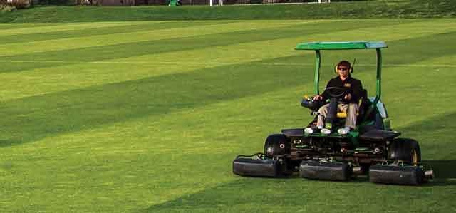 man operating John Deere turf equipment on a sports field