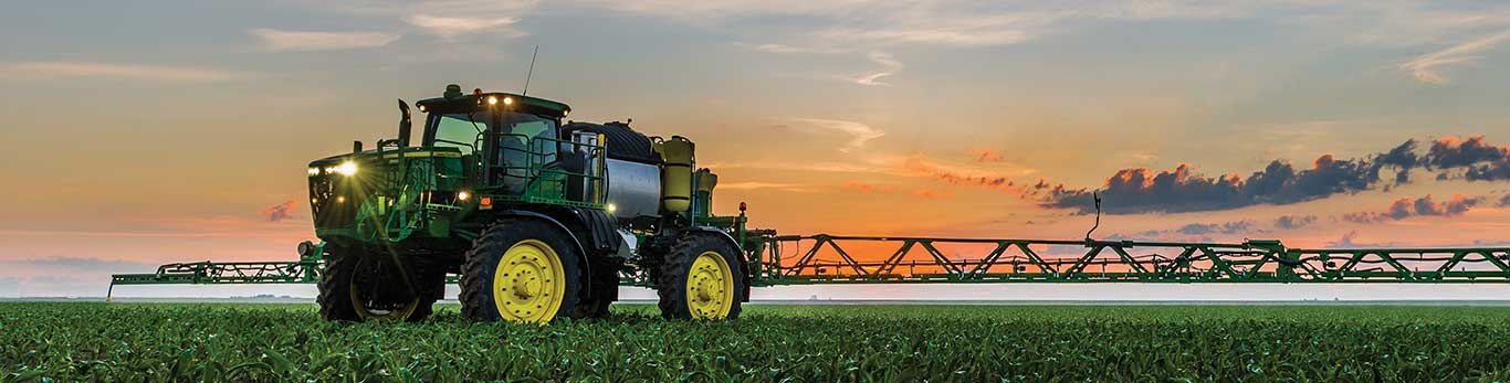 Self propelled sprayer in the field at dusk