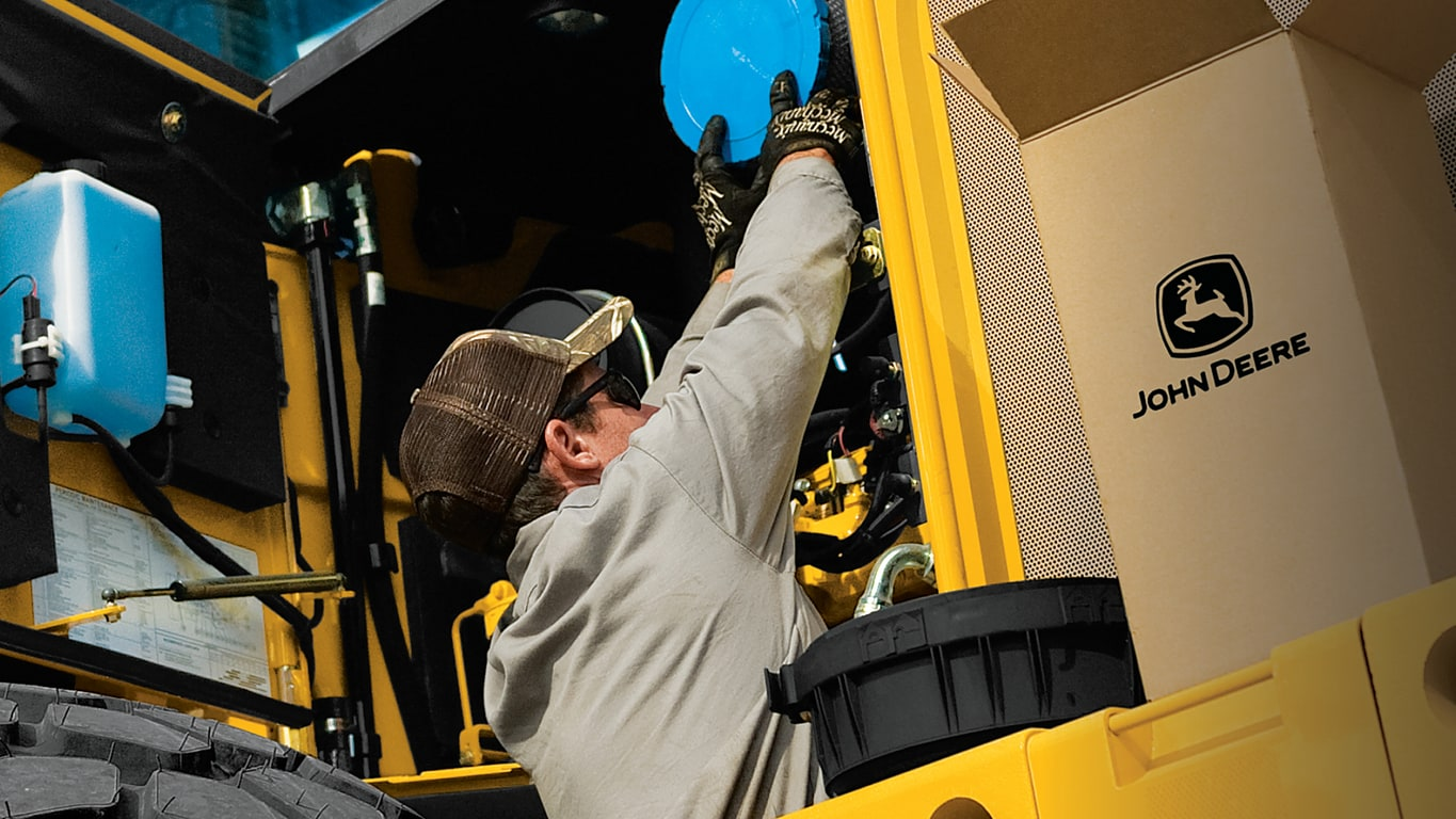 Image of a man replacing parts on John Deere equipment.