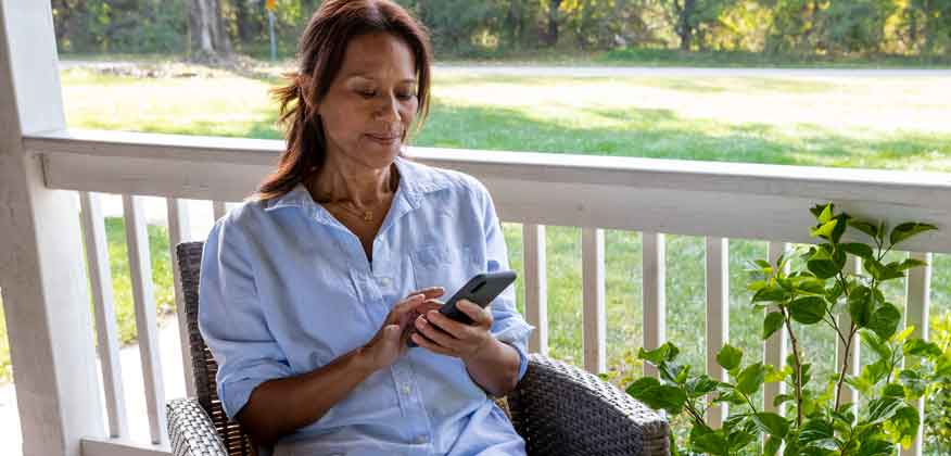 Woman sitting on a chair on her porch looking at her cell phone
