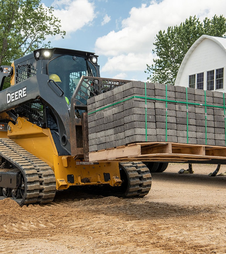 325G Compact Track Loader with forks attachment hauls a load of landscaping blocks in front of a white barn.