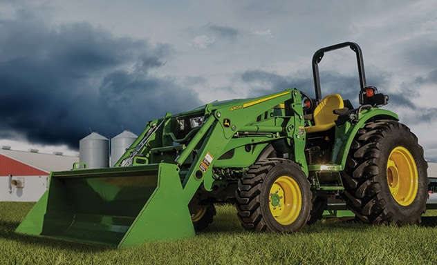 4M Heavy-duty Compact Utility Tractor with a loader sitting in a field of grass with a barn in background.