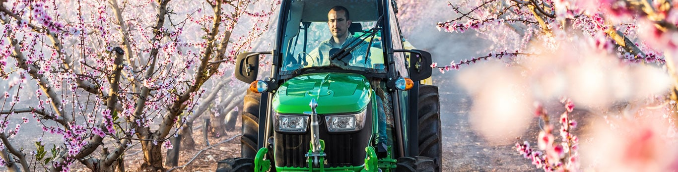 Man drives specialty tractor between rows of trees with beautiful pink blossoms.