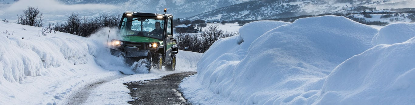 John Deere Gator with snow blade attachment clears snow on snow-covered path.