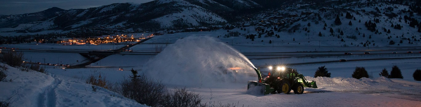 Tractor with snow-throwing attachment moves snow outside of mountain town.