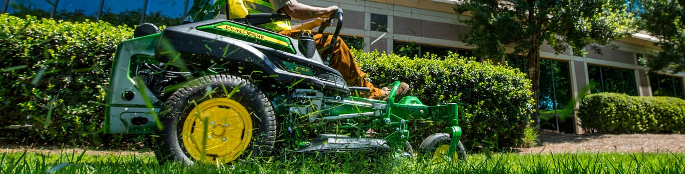 Z915E lawn tractor mows grass in front of a building.