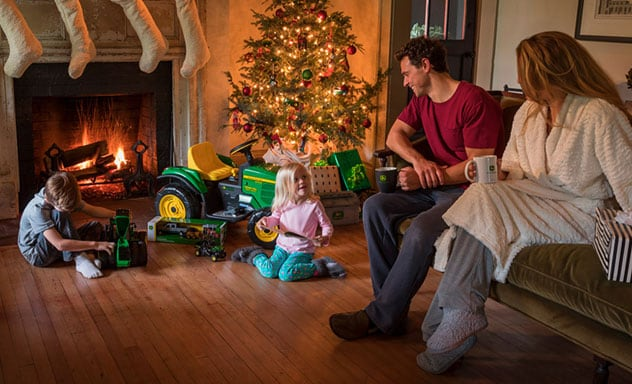 Family on Christmas morning sitting around a fireplace and brightly lit Christmas tree opening John Deere toy tractors and gifts.