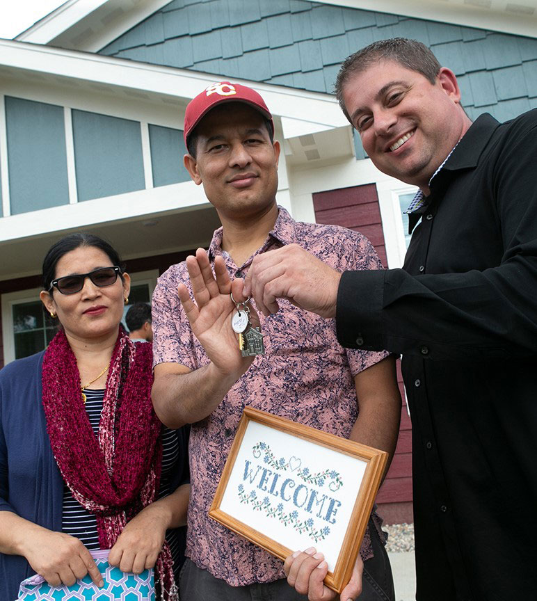 Man handing keys to couple standing in front of their new house