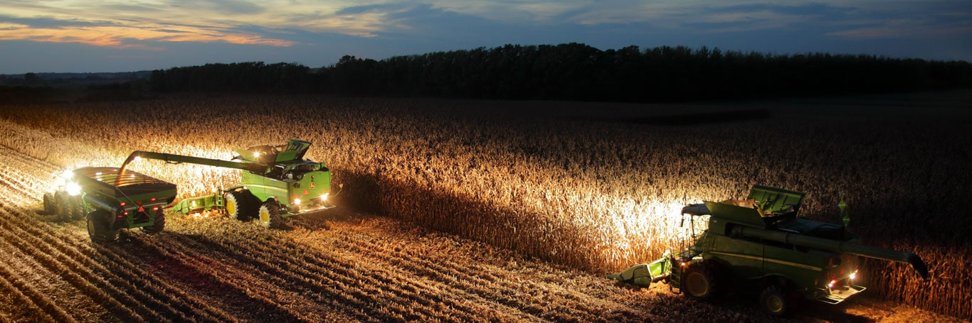 Two combines work at night in a field