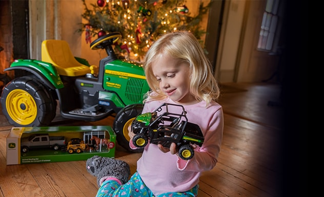 Girl smiles while holding toy John Deere Gator. She is surrounded by a fireplace, Christmas tree and other toys.