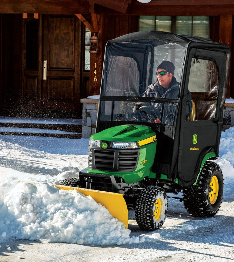 Man plowing snow on John Deere riding mower with cab and plowing attachments.