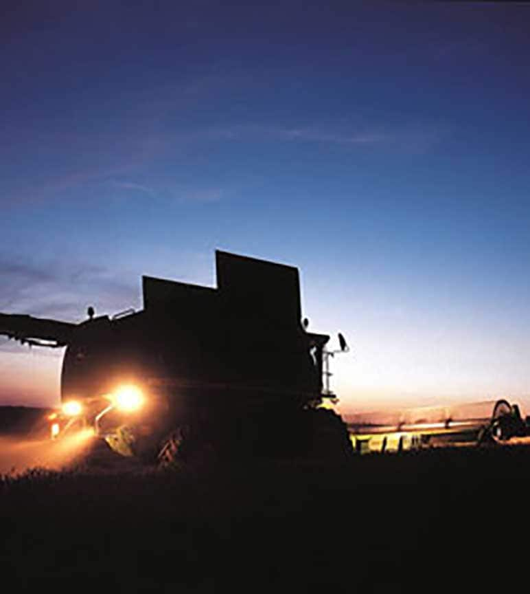 Combines in the field at sunset