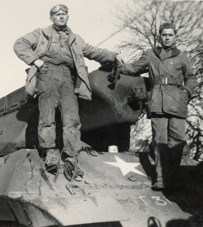 Two world war two soldiers stand on a tank