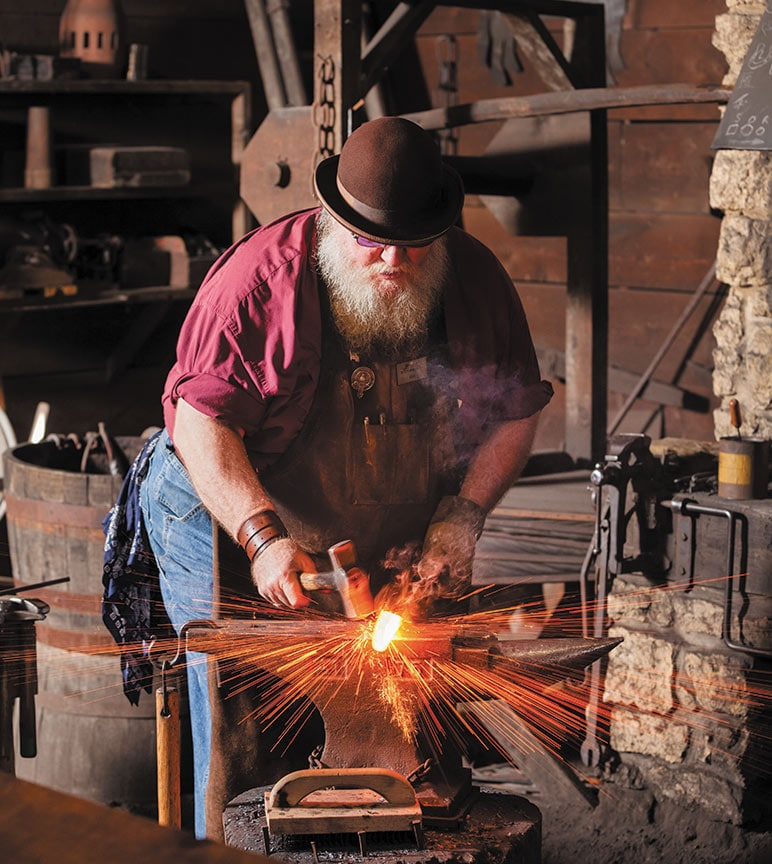 Image of blacksmith Rick Traham hammering metal.