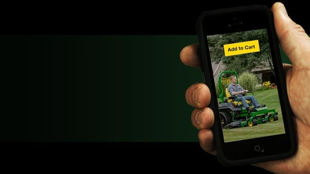 Hand holding mobile phone on Add to cart mower page.