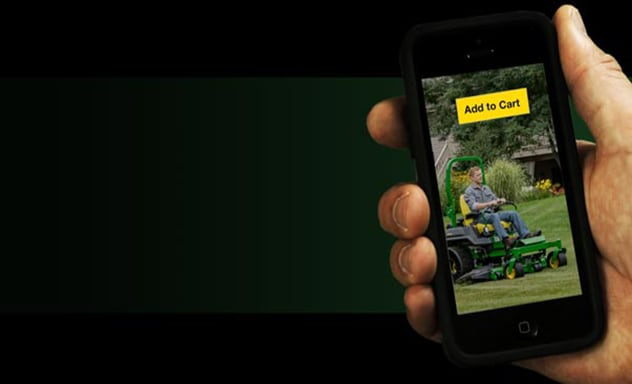 Hand holding mobile phone which displays a man riding lawn mower with Add to Cart button on screen.