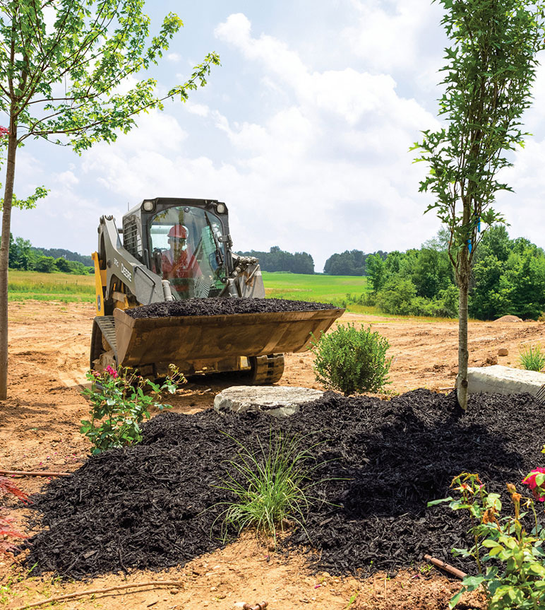 317G Compact Track Loader hauls a bucket of mulch to a landscaping bed