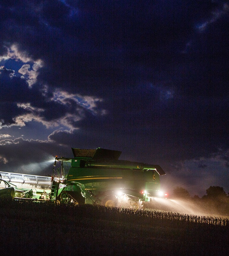 Combine harvesting wheat at night in the rain.